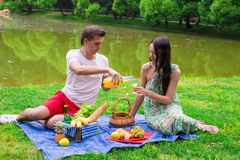 Young happy couple picnicking outdoors near the Royalty Free Stock Photos