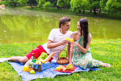 Young happy couple picnicking outdoors near the Royalty Free Stock Images