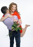 Young happy couple with pink roses Stock Image