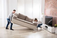 Couple Placing Sofa At Their New Home. Young Happy Couple Placing Sofa At Their New Home royalty free stock photos