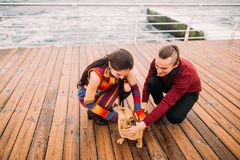 Young happy couple playing with dog on the rainy berth in autumn. Sea background.  Royalty Free Stock Image