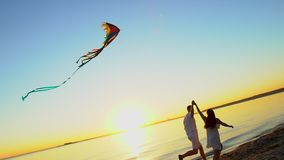 Young happy couple playing with a kite on the sea beach at sunset. Man and woman enjoying time together at beach of sun stock footage