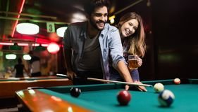 Young couple playing snooker together in bar. Young happy couple playing snooker together in bar stock photo