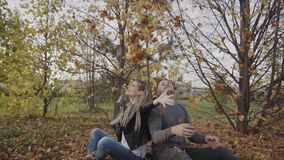 Young happy couple playing and throwing leaves in the autumn park. HD stock video