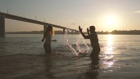 Young happy couple playing in the water. They are against sunset background stock video footage