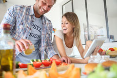Young happy couple preparing dinner in the kitchen Royalty Free Stock Photos