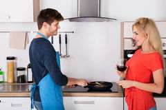 Young Happy Couple Preparing Dinner In Kitchen Royalty Free Stock Image
