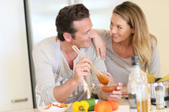 Young happy couple preparing meal Stock Photos