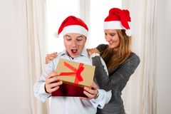Young Happy Couple with Presents on rug at Christmas Royalty Free Stock Photos