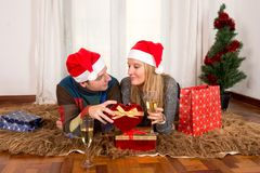 Young Happy Couple with Presents on rug at Christmas Royalty Free Stock Images