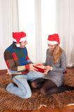 Young Happy Couple with Presents on rug at Christmas Royalty Free Stock Photo