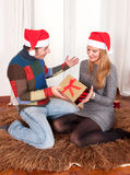 Young Happy Couple with Presents on rug at Christmas Stock Photo