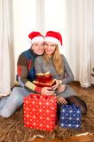 Young Happy Couple with Presents on rug at Christmas Stock Image