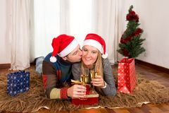 Young Happy Couple with Presents on rug at Christmas Royalty Free Stock Photography