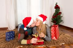 Young Happy Couple with Presents on rug at Christmas Royalty Free Stock Image