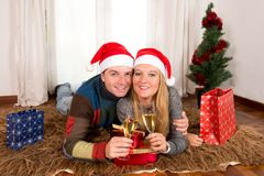 Young Happy Couple with Presents on rug at Christmas Stock Photography