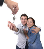 Young happy couple receiving house key new residence in real state concept. Young happy couple receiving the house key of their new flat or apartment in stock photography