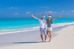 Young happy couple in red Santa hats on tropical Royalty Free Stock Photos