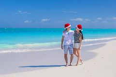 Young happy couple in red Santa hats on tropical Royalty Free Stock Photography