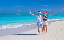 Young happy couple in red Santa hats on tropical Stock Photo