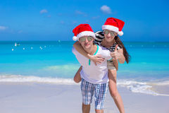 Young happy couple in red Santa hats on white Royalty Free Stock Photography