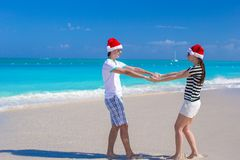 Young happy couple in red Santa hats on white Royalty Free Stock Photo