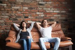 Young happy couple relaxing on comfortable leather couch at home. Relaxed smiling men and women resting on sofa in loft interior breathing fresh air meditating Royalty Free Stock Images