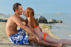 Young happy couple relaxing & kissing on sandy sea beach embracing. Happy couple together on sandy beach embracing & kissing on summer sea outdoors background Royalty Free Stock Images