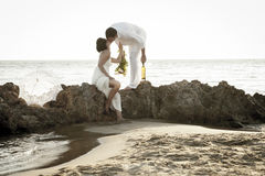 Young happy couple relaxing together on beach rocks at sunrise Stock Photo