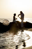Young happy couple relaxing together on beach rocks at sunrise. Young happy couple relaxing together on beach rocks Royalty Free Stock Photography