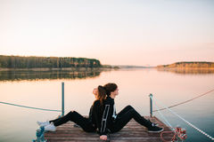 Young happy couple resting on a pier on a sunny summer day. Love concept Royalty Free Stock Photography
