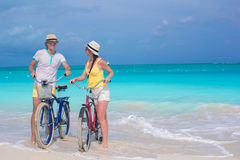 Young happy couple riding bikes on white tropical beach Royalty Free Stock Photography