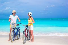 Young happy couple riding bikes on white tropical Royalty Free Stock Photography