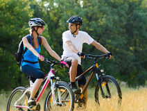 Young Happy Couple Riding Mountain Bikes Outdoor Stock Photo
