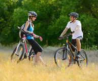 Young Happy Couple Riding Mountain Bikes Outdoor Royalty Free Stock Images