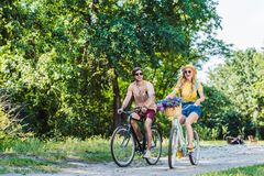 young happy couple riding retro bicycles in park stock image