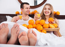 Young happy  couple with ripe oranges and freshly juice Stock Image