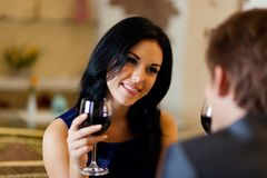 Young happy couple romantic date drink glass of. Red wine at restaurant, celebrating valentine day Stock Photos