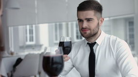 Young happy couple romantic date drink glass of red wine at restaurant, celebrating valentine day Stock Image