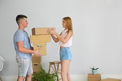 Young happy couple in room with moving boxes royalty free stock photos