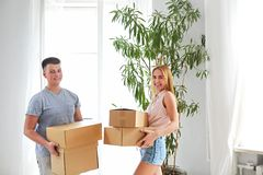 Young happy couple in room with moving boxes Stock Photos