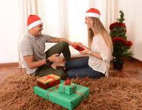 Young Happy Couple on rug at Christmas with Presents royalty free stock photos
