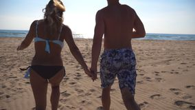 Young happy couple running at the beach to the sea and holding hands of each other. Girl and boy having fun together at. Summer vacation or holiday. Close up stock video