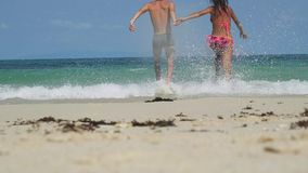 Young happy couple running at the beach to the sea and holding hands of each other. Girl and boy having fun together at stock video footage