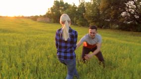 Young happy couple running on a field at sunset. stock footage