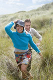 Young happy couple running through grass at beach stock photos