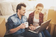 The young happy couple searching for apartments with laptop. Moving, purchase of new habitation stock images