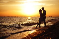 Young happy couple on seashore. Young happy couple on seashore in the lights of sunset royalty free stock photo