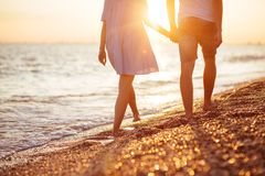 Young happy couple on seashore. Young happy couple on seashore in the lights of sunset stock images