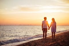 Young happy couple on seashore. Young happy couple on seashore in the lights of sunset royalty free stock photography